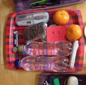 Kuvituskuva ylioppilaskokeeseen vietävästä tarjottimesta. Tarjottimella leipää, hedelmiä, juomaa, harppi.